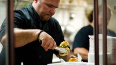 Michell Sánchez prepara un par de hamburguesas en su camión gourmet.