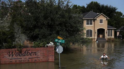 Un residente de Houston camina en terrenos inundados luego del hurac&aac...