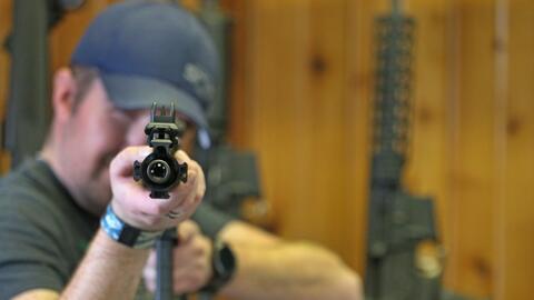 Un hombre prueba un rifle semi automático AR-15 en una armer&iacu...