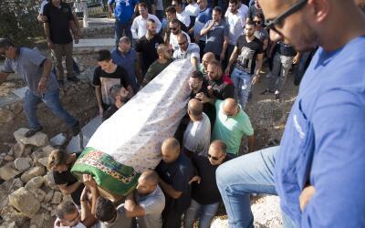 Varios hombres cargan el cadáver de Yussef Utman, uno de los guar...