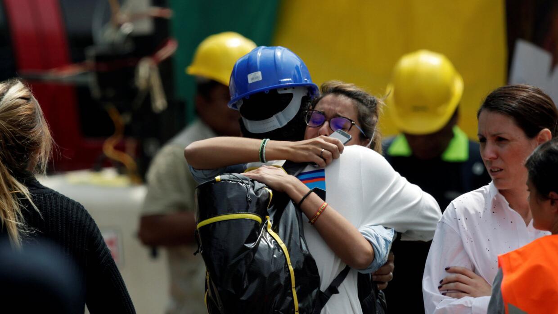 Una persona que tiene un familiar atrapado entre los escombros abraza a...