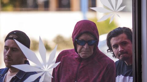 Un grupo de personas hace fila en una tienda de marihuana en Los Angeles...